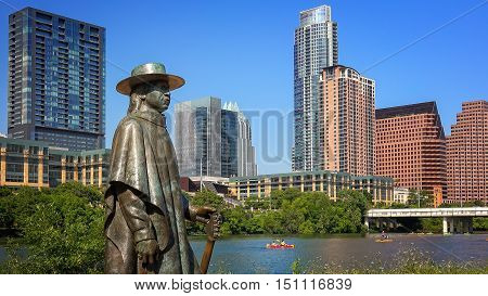 AUSTIN, TEXAS - APRIL 9: Stevie Ray Vaughan statue in front of downtown Austin and the Colorado River in Austin, Texas on April 9th, 2016.