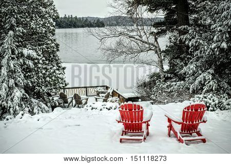Pair of wooden adirondack chairs in the snow in front of the frozen lake