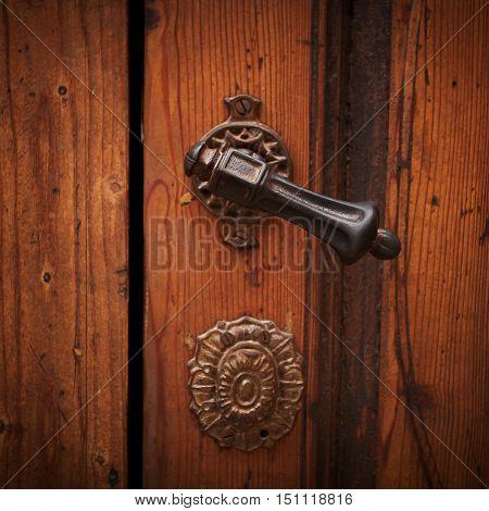 Ancient door handle on a wooden door