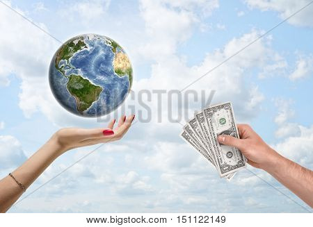 Man's hand giving dollar bills to a female hand, which supports the planet Earth. Donating money to worldwide conservation and environmental organizations. Environment and ecology. Save planet. Elements of this image are furnished by NASA.