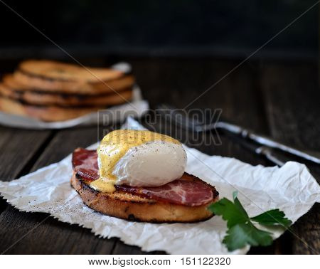 Poached with bacon and toast, parsley on paper, fork on a dark wooden background