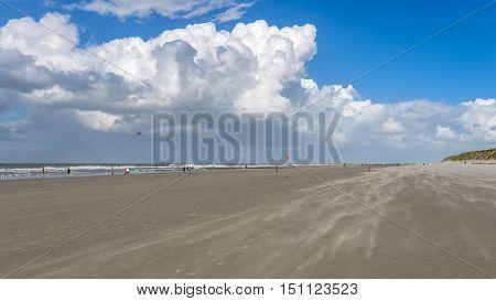 People Enjoy A Walk Along A Sandy Beach On The North Sea
