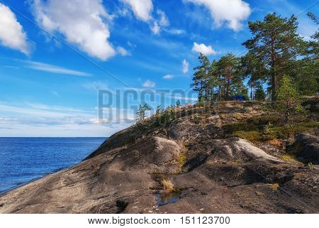 Blue tourist tent on a high rocky shore of Lake Ladoga on the background of blue sky with white clouds in Karelia.