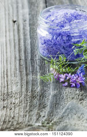 bath salt in a clear glass jar and purple flowers on a rough wooden board