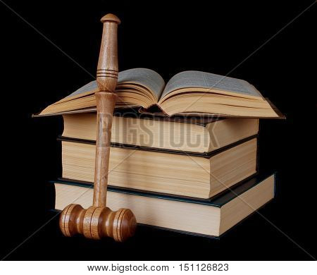 Wood gavel and stack of thick old books on a black background