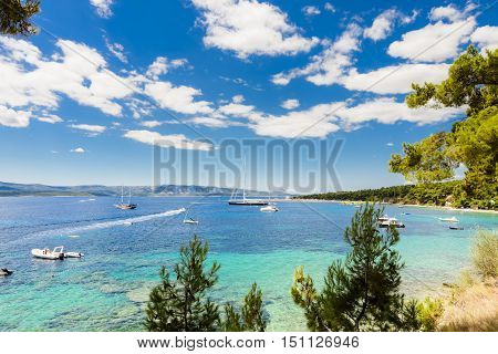 BOL, ISLAND BRAC, CROATIA - JULY 17, 2016: Zlatni rat beach crowded with swimmers, surfers and boats in high season