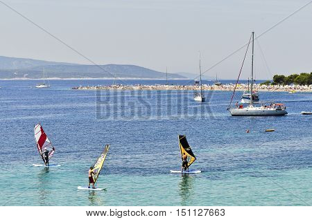 BOL, ISLAND BRAC, CROATIA - AUGUST 14, 2011: Surfing school at Zlatni Rat, famous turquoise beach in Bol on Brac island Dalmatia Croatia