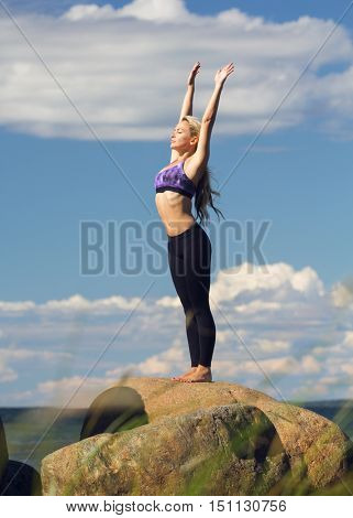 young caucasian fitness woman practicing yoga at sea shore