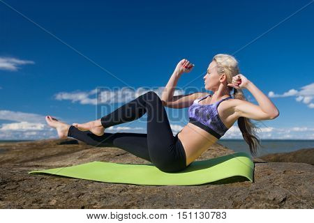 caucasian woman duing abs exercise at the seashore during summer training