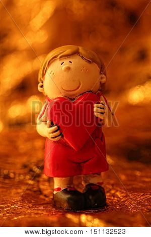 Statuette Cute Boy holding heart on an abstract yellow background bokeh