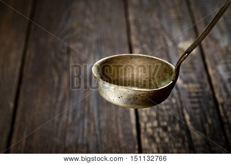 old metal soup ladle on the dark wooden background