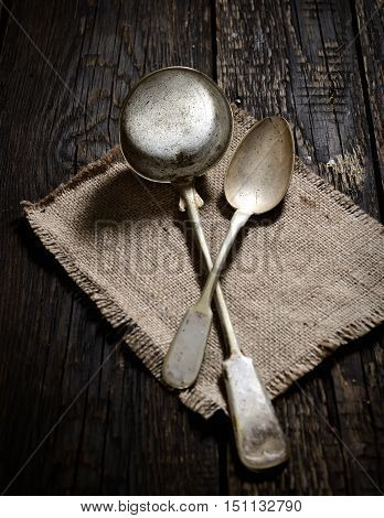 vintage soup ladle   and spoon on a napkin on a dark wooden background