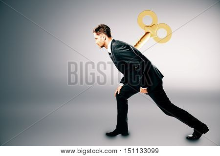 Young businessman with wind up key on his back. Light grey background. Control concept