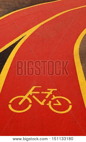 Yellow bicycle sign on red bicycle lane