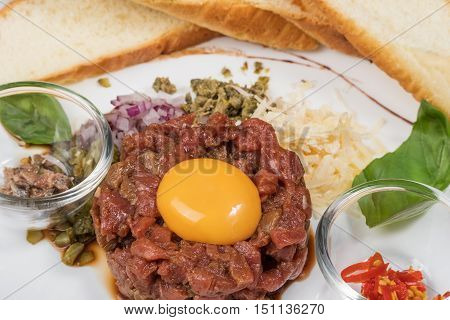 Delicious classic steak tartar with herring pepper onion and slices of bread close-up