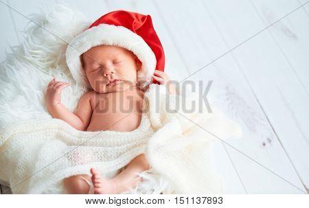 sleeping newborn baby in a Christmas Santa cap