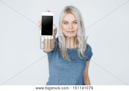 Focus on phone. Woman showing smartphone screen to the camera. cute blond teenage girl with smart phone in the foreground.