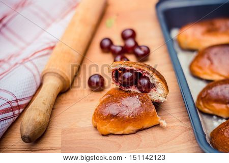 Oven fresh home made baked patties stuffed with cherry. Delicious pastries on a baking sheet surrounded by cherry napkin and rolling pin.