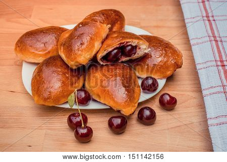Oven fresh home made baked patties stuffed with cherry. Delicious pastries on a baking sheet surrounded by cherry napkin