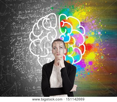 Girl in black cardigan standing near blackboard with colorful brain sketch and formulas on it. Concept of scientific discovery.