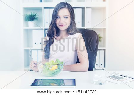 Business lady eating salad at her table at work in office. She is smiling and enjoying her lunch break. Concept of healthy lifestyle and dieting. Toned image