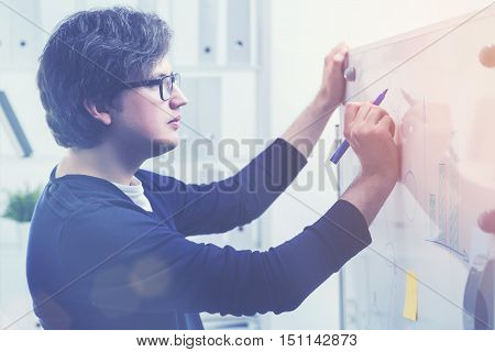 Man Drawing Charts On Whiteboard With Memos