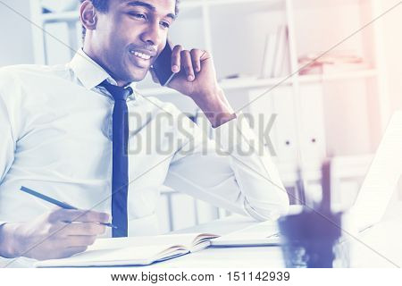 Side view of young african american businessman using notepad and laptop on office desktop while having a mobile phone conversation. Toned image