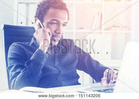 Man On Phone Using Laptop In Sunlit Office