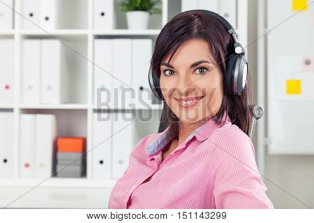Cheerful hotline worker is looking to the camera with crazy eyes and smiling. Concept of office routine