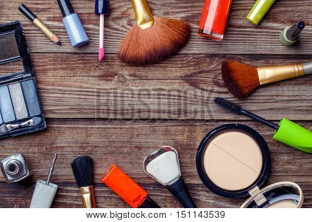 Various make-up products laid on wooden table. Copy space