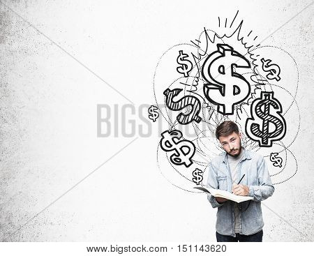 Portrait of man in casual clothes standing with his notebook near concrete wall with shining dollar symbols. Concept of earning big bucks. Mock up