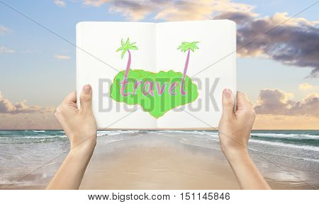 Hands holding book with creative travel sketch on seaside background. Vacation concept