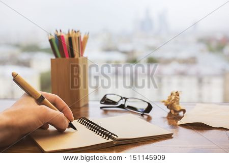 Closeup of hand writing in spiral notepad placed on wooden windowsill with glasses colorful pencils and other items