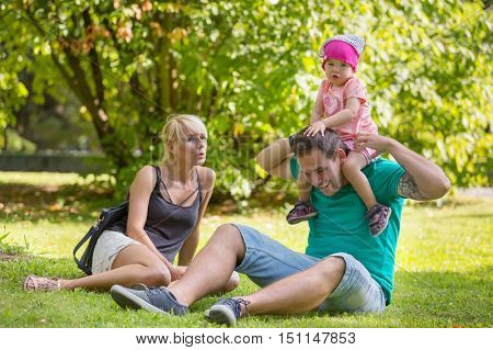 Parents with their little daughter in the park