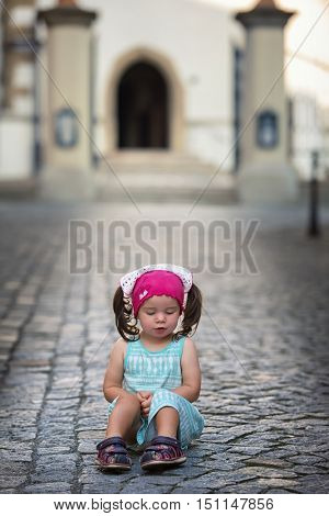 Cute baby sitting on the street outside the medieval city