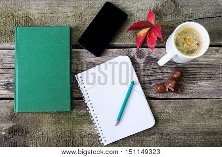 Smartphone, A Notebook For Writing, A Book And A Cup Of Coffee. Frame Composition On Vintage Board B