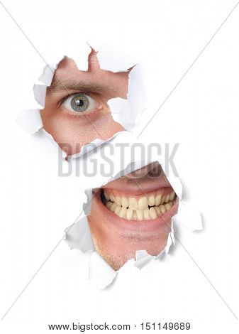 Spooky man looking through a hole in paper
