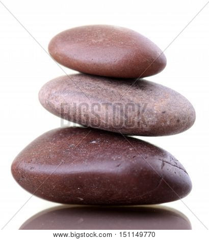 Pile of zenlike stones isolated on white background with reflexion