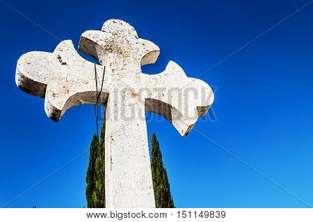 Horizontal photo in color of white christian cross and blue sky