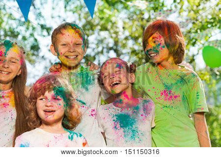 Five happy kids, age-diverse boys and girls, smeared with colored powder, standing together outside