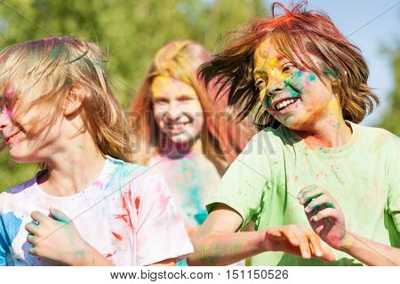 Cute kids celebrate Holi festival with colored powder on faces and body