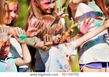 Children painted in the colors of Holi festival putting their hands up and showing colored palms