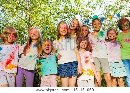 Big group of age-diverse kids, smeared with colored powder, standing together in a row outside in summer
