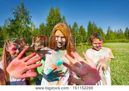 Portrait of happy beautiful young girl on color festival with smeared palms and face