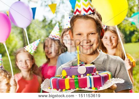 Portrait of smiling young boy in party hat holding birthday cake, standing among his friends at the outdoor party