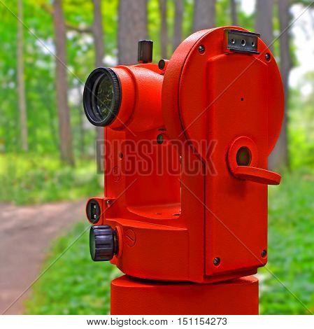 Red micrometer theodolite against blur summer garden