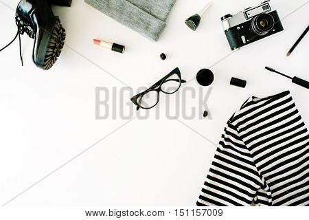 flat lay feminine autumn and winter clothes collage with retro camera accessories and cosmetics on white flat lay top view