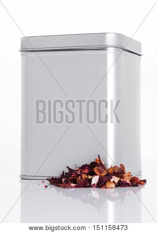 Fruit tea steel jar with loose tea next to it on white background