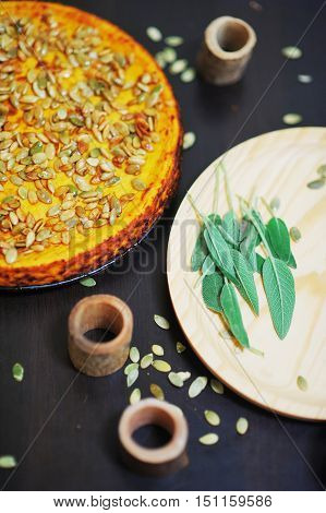 Air Pumpkin Pie, Sprinkled With Seeds On A Black Table Next To A Wooden Board Sage Leaves, Top View