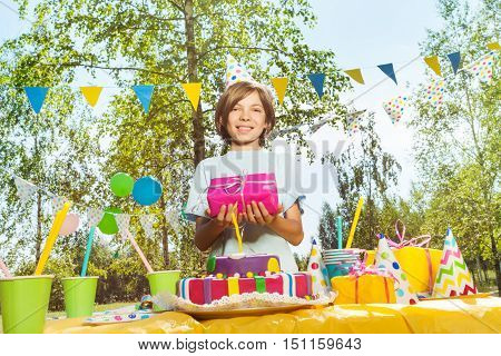 Happy young boy in birthday hat holding box in pink gift wrapping, standing next to the table with B-day cake